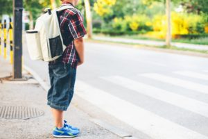 child waiting for school bus